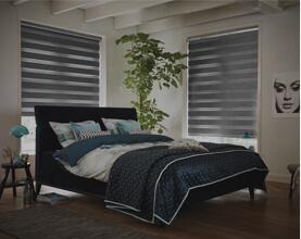 To nedrullede rullegardiner der mørklægger soveværelse